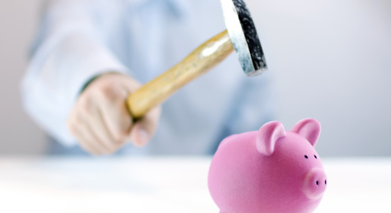 Pink piggy bank and hand with hammer
